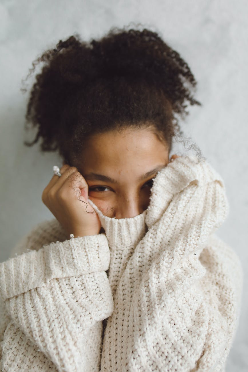 woman in white knit sweater covering her face with her hands