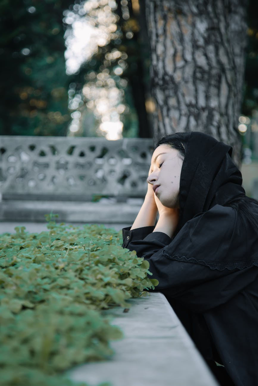 mindful woman leaning on hands in graveyard
